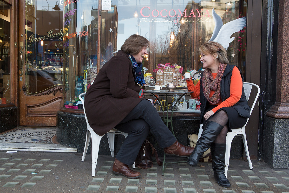 Two women sitting and chatting outside a cafe. One woman has a cochlear implant.