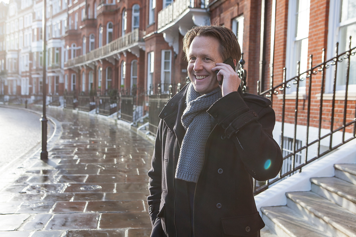 A man standing outside on the phone with an Advanced Bionics cochlear implant